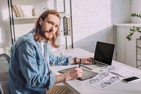 barbu d'animateur dans des écouteurs sans fil près de gadgets Banque d'images