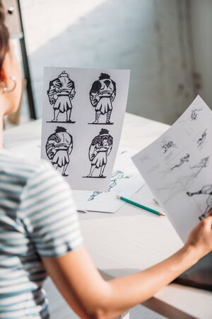 selective focus of illustrator holding papers with sketches Banque d'images
