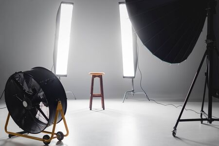 digital camera, fan, reflector, wooden stool and lights on backstage in photo studio Imagens