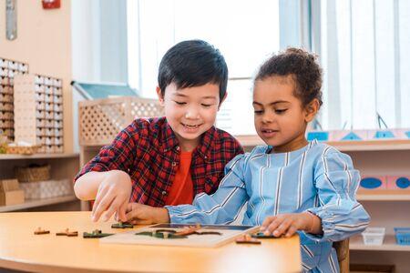 Niños jugando con juego de mesa de madera en la mesa en clase montessori