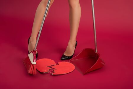 partial view of sexy girl in high heeled shoes sweeping broken paper heart with broom and scoop on red background Stock Photo