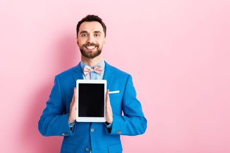 happy businessman holding digital tablet with blank screen on pink Banque d'images