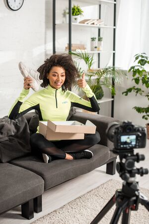 selective focus of cheerful african american influencer in braces showing thumb up and holding new sneaker near digital camera