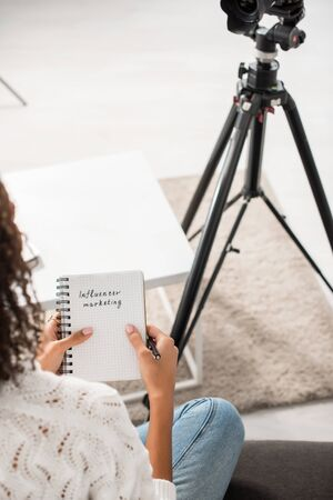 cropped view of curly african american girl holding notebook with influencer marketing lettering at home