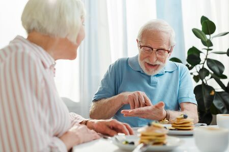 Selective focus of senior man talking to wife by coffee and pancakes on table