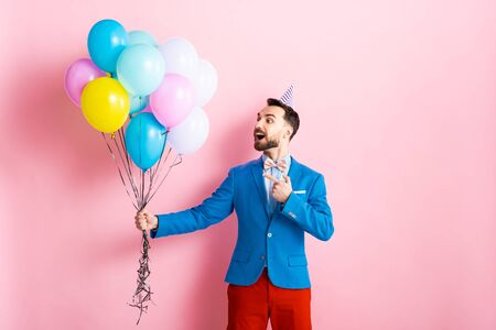 happy man in suit pointing with finger at balloons on pink