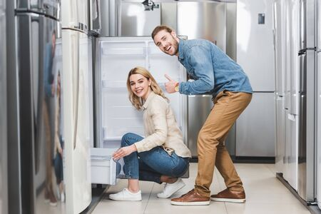 smiling boyfriend showing like and girlfriend sitting near new fridge in home appliance store