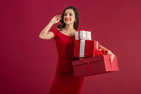 sexy, happy girl looking away and waving hand while holding gift boxes isolated on red
