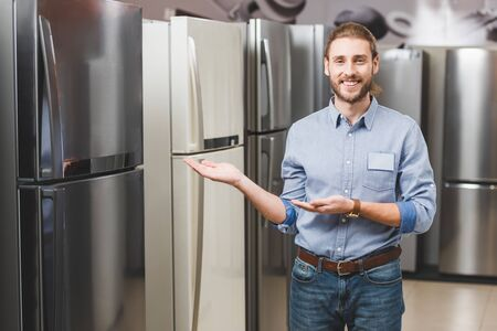 smiling consultant pointing with hands at fridge in home appliance store