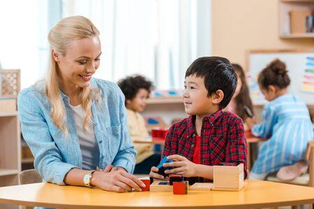 Selectieve focus van lachende leraar en kind die bouwstenen speelt met kinderen op de achtergrond in montessorischool