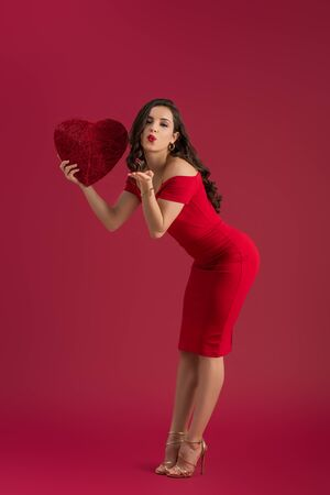 flirty, elegant girl holding decorative heart and sending air kiss at camera while standing on red background