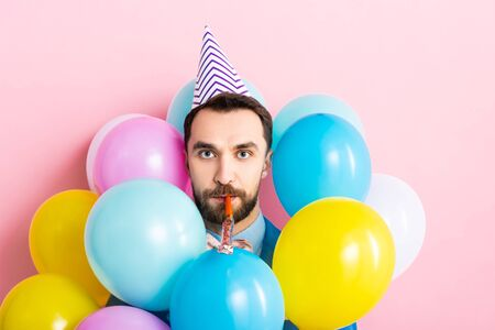 bearded man in party cap with party blower in mouth near balloons on pink Foto de archivo