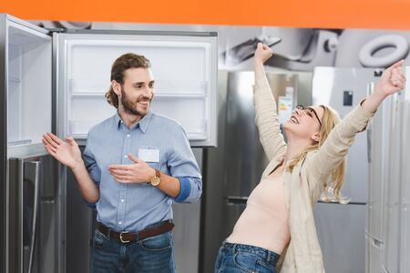 consultant pointing with hands at fridge and smiling woman showing yes gesture in home appliance store