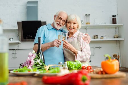 Selective focus of elderly couple smiling at camera while clinking with champagne by vegetables and bouquet on kitchen table