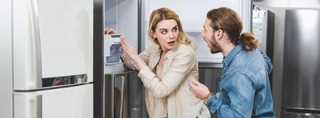 panoramic shot of shocked boyfriend and girlfriend standing near fridge in home appliance store