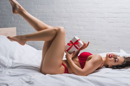 passionate, happy girl in red lingerie lying in bed with raised legs and holding white gift box