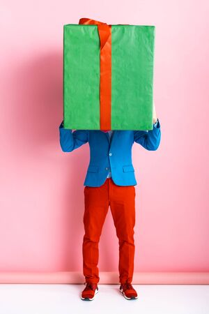 man in suit covering face while holding huge present on pink 免版税图像