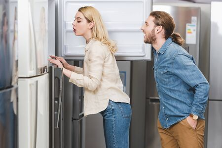 side view of shocked boyfriend and girlfriend looking at fridge in home appliance store
