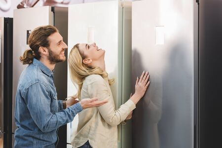 side view of smiling boyfriend pointing with hand and girlfriend touching fridge in home appliance store