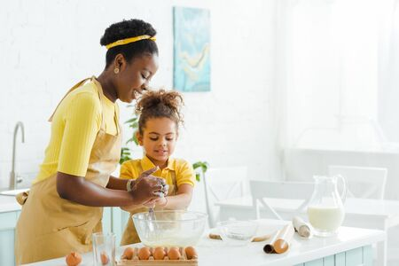 adorable african american kid and cheerful mother smiling while cooking in kitchen Imagens