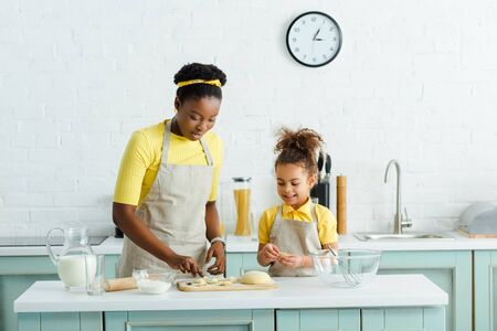 african american mother and daughter sculpting dumplings near jug with milk in kitchen