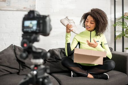 selective focus of sportive african american influencer in braces holding new sneaker near box and digital camera Stock Photo