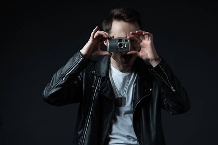 stylish brutal man in biker jacket taking picture on film camera with open mouth isolated on black Stock Photo