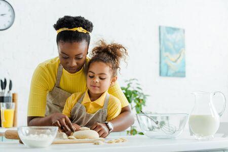african american mother near adorable kid sculpting dumplings in kitchen Standard-Bild