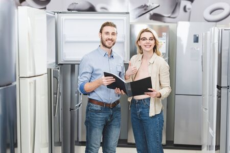 smiling consultant holding folder and woman showing like in home appliance store