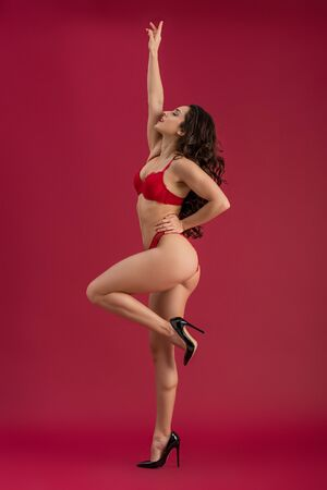 side view of sexy girl in lingerie and high heeled shoes posing with raised hand on red background