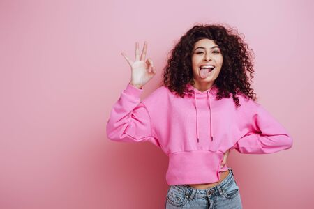 cheerful bi-racial girl sticking out tongue and showing okay gesture on pink background Stock Photo