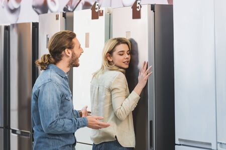 girlfriend touching fridge and shocked boyfriend looking at her in home appliance store