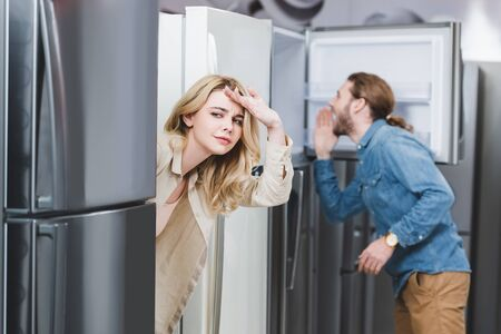 selective focus of curious girlfriend and boyfriend looking at fridge on background in home appliance store
