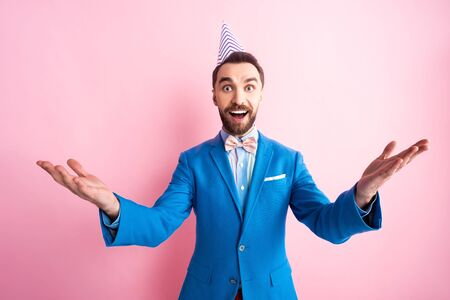 excited businessman in party cap with outstretched hands looking at camera on pink Banque d'images