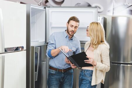 consultant pointing with hand at folder and talking with woman near fridges in home appliance store