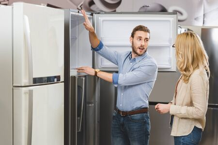 consultant talking with woman and showing fridge in home appliance store