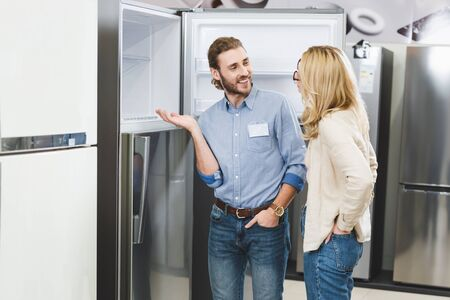 smiling consultant pointing with hand at fridge and talking with woman in home appliance store