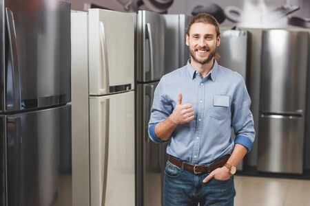 smiling consultant showing like near fridges in home appliance store