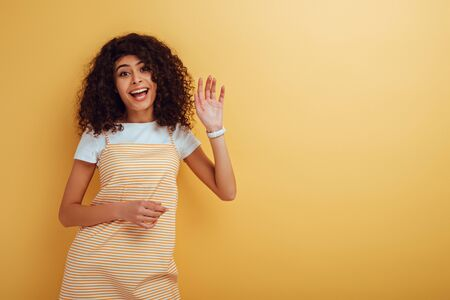 happy mixed-race girl waving hand while looking at camera on yellow background