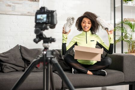 selective focus of happy and sportive african american influencer in braces holding new sneakers near box and digital camera