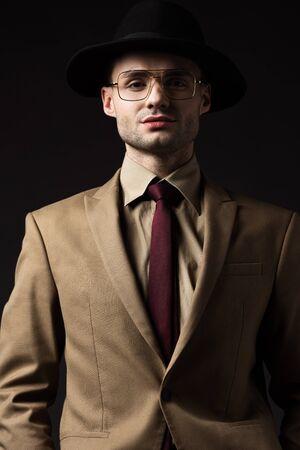 Hombre elegante confiado en traje beige, sombrero y anteojos aislados en negro