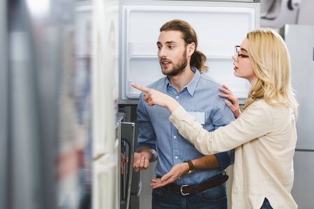 woman talking with consultant and pointing with finger at fridge in home appliance store
