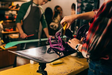 cropped view of worker screwing snowboard binding to snowboard in repair shop Stock Photo