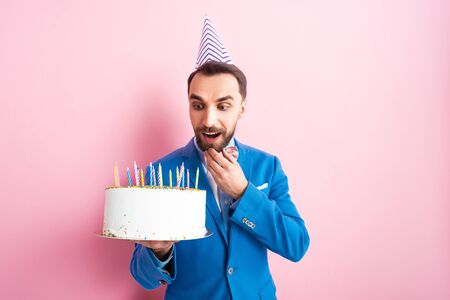 surprised bearded man looking at birthday cake on pink