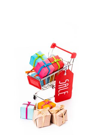 decorative small shopping cart with gift boxes and price tag with sale lettering isolated on white Stock Photo