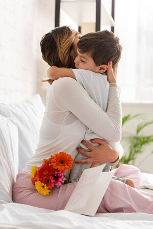 happy mother hugging adorable son while sitting in bed near flowers and mothers day card