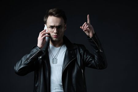 tense stylish man in leather jacket talking on smartphone and showing idea gesture isolated on black