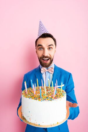 happy businessman in party cap holding birthday cake with candles on pink Banque d'images
