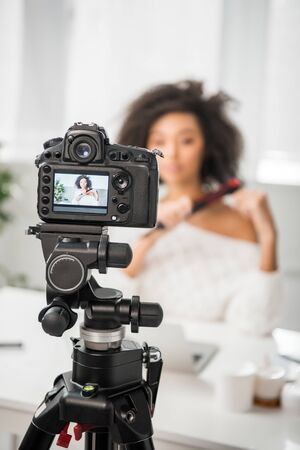selective focus of digital camera with curly african american influencer using hair straightener on display 스톡 콘텐츠