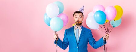 panoramic shot of businessman in party cap holding balloons on pink Banque d'images